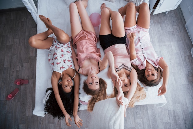 Full height. inverted portrait of charming girls that lying on bed in nightwear. top view