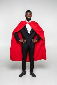 Полный рост африканского человека в костюме и пальто супермена