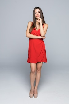 벽에 걸어 슬림 빨간 드레스를 입고 매력적인 패션 여자의 전체 높이.