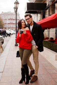 日付または休日に通りを歩いて恋にファッショナブルなエレガントなカップルの完全な高さの屋外イメージ。カメラで写真を作る赤いセーターのブルネットの女性。