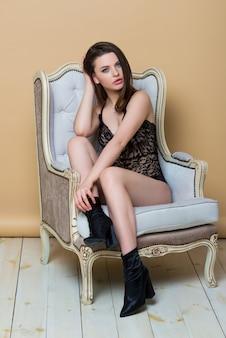 전체 높이 초상화. 빈티지 의자에 앉아 섹시 블랙 끈 콤보 죄수 복에 아름 다운 갈색 머리 소녀. 패션 란제리. 럭셔리 여자.