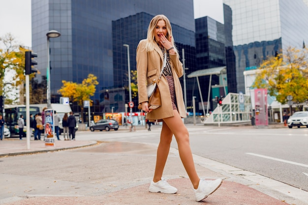Full height portrait of pretty blond woman posing over urban street. wearing beige coat and white sneakers. trendy accessories. carefree lady walking along the street.