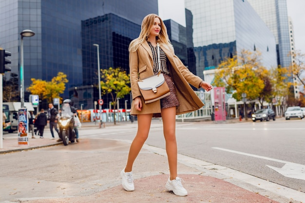 Full height portrait of pretty blond woman posing over urban. wearing beige coat and white sneakers. trendy accessories. carefree lady walking along the street.