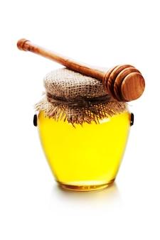 Полный горшок меда и медовая палочка на белом