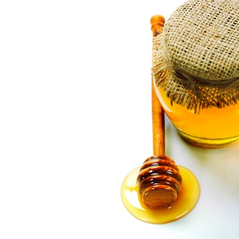 Full honey pot and honey stick on white with copyspace