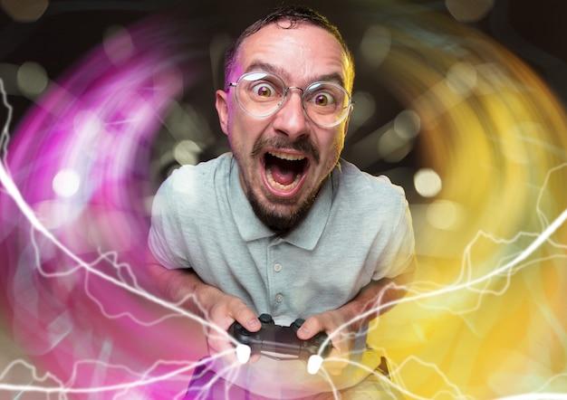 ゲームプレイに完全に没頭するカラフルで隔離されたビデオゲームコントローラーを保持している若い男