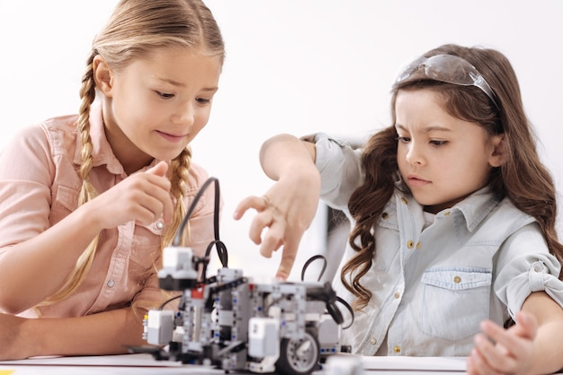 Full of interest. smiling amused curious kids expressing joy and touching robot while having tech class