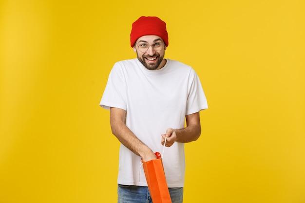쇼핑 가방을 여는 젊은 남자에서 완전 격리 된 스튜디오 사진. 노란색 위에 분리하십시오.