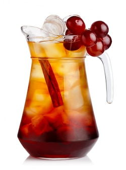 Full jug of fresh nonalcoholic cocktail with grapes and cinnamon stick