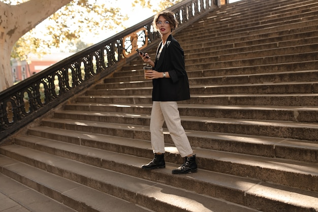 Full leght woman in boots, jacket and white trousers hold phone and cup of tes outside. modern woman in eyeglasses posing