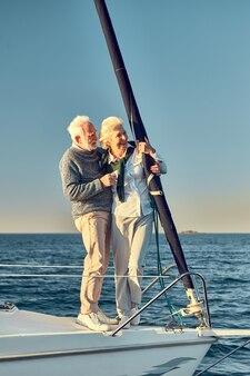 の側に立っている愛の引退した男と女の美しい幸せな年配のカップルの完全な長さ