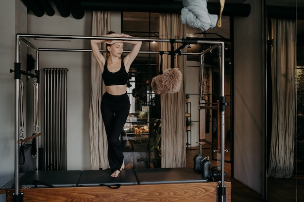 Full leghth of young slim fitness woman in black sportswear leaning forward standing on pilates cadillac reformer and resting, doing stretching exercises in gym. healthy lifestyle and sport concept