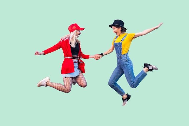 세련된 옷을 입은 두 명의 행복한 비명을 지르는 세련된 힙스터 소녀의 전신 크기 초상화가 공중으로 뛰어올라 승리를 축하하고 있습니다. 실내 스튜디오 촬영, 녹색 배경에 고립