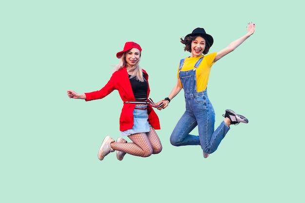 세련된 옷을 입은 두 명의 행복한 비명을 지르는 세련된 힙스터 소녀의 전신 크기 초상화가 공중으로 뛰어올라 카메라를 바라보고 있습니다. 실내 스튜디오 촬영, 녹색 배경에 고립