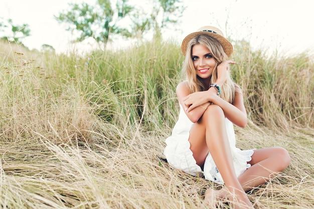 干し草のカメラにポーズをとって長い髪のかわいいブロンドの女の子の完全な水平写真。彼女は帽子と白いドレスを着て、カメラに微笑みかけます。