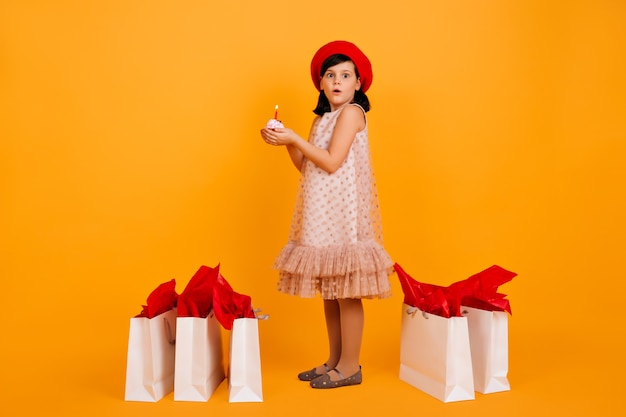 Full lengh shot of little girl with shopping bags. cute kid in red french beret isolated on yellow wall.