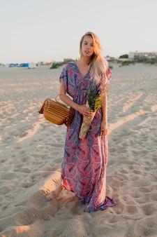 Полное изображение красивой белокурой женщины с букетом лаванды, идущей на пляже. цвета заката.