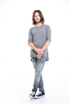 Полная длина красивого молодого человека с длинными волосами, стоящего на белом фоне