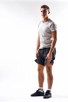 Полная длина спортсмена в шортах и белой футболке