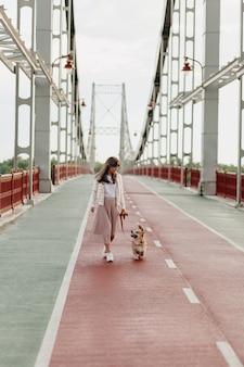 コーギーと一緒に歩いている明るい橋を歩いている女性のフルレングス