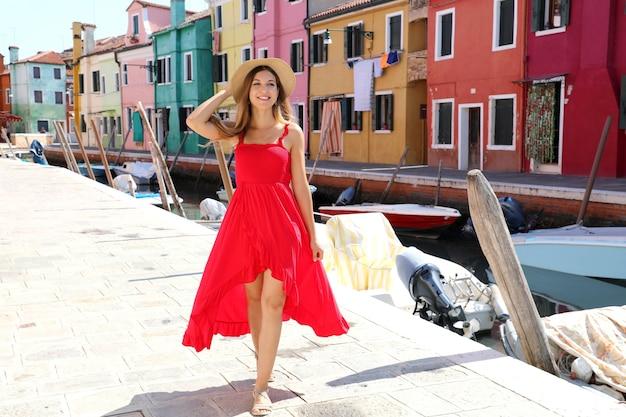 イタリア、ヴェネツィアのブラーノ色のカラフルな町で若い美しいダンサーの女の子の完全な長さ