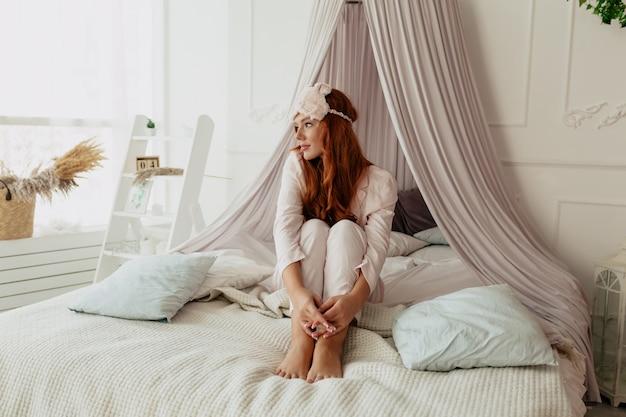 Foto a figura intera di una donna adorabile con un lungo har ondulato che indossa un pigiama rosa che si sveglia la mattina nel letto