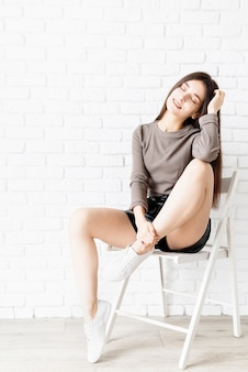 Full lenght portrait of a beautiful brunette woman with long hair wearing brown shirt and black leather shorts sitting on the chair