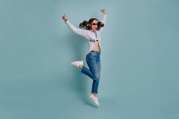 孤立した壁を飛び越えて楽しんでいる面白い素敵な女性モデルの完全な長さの肖像画。幸せな女の子のダンスと青い孤立した背景に笑顔。