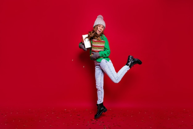 Полноразмерный портрет счастливой стильной молодой леди, одетой в зеленый свитер, синие джинсы, черные ботинки и серую зимнюю кепку, прыгающую с новогодними подарками на изолированном красном фоне