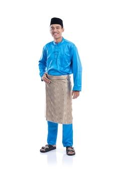 白い背景の上の青い伝統的なサテンの服とマレーシアの男性の完全な長さの肖像画