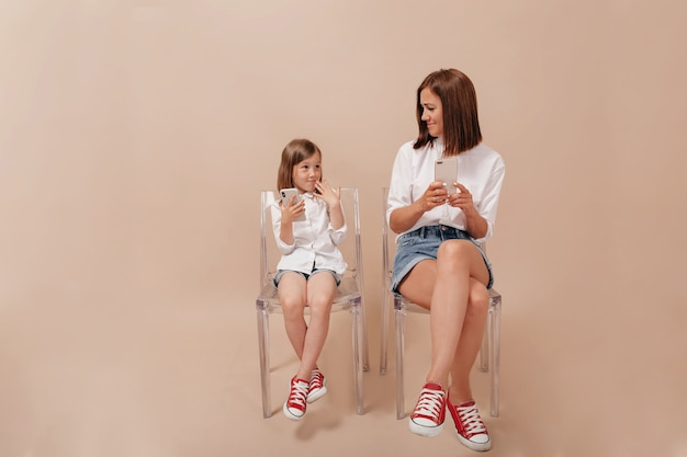 Full-lenght portrait of pretty woman with little daughter using smartphones over beige background