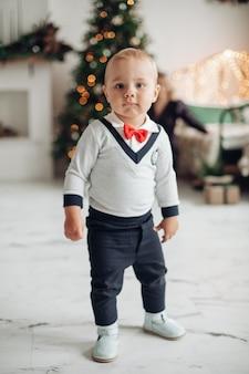Ritratto a figura intera di un bambino alla moda con fiocco rosso in piedi nel soggiorno decorato per natale