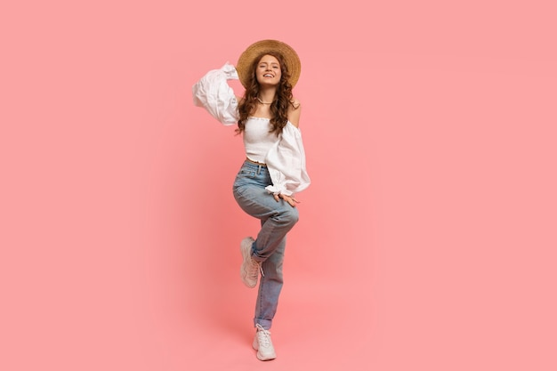 Full lenght portrait of woman in elegant linen top with balloon sleeves and blue jeans posing on pink