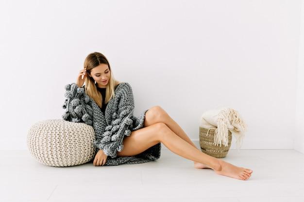 ブロンドの髪と優しい笑顔で孤立した白い壁にポーズをとってニットセーターを着ている美しい裸の脚を持つ魅力的な女性モデルのフルレングスショット