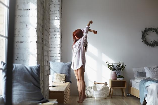 寝室でつま先に裸足で立って体を伸ばし、腕を上げ、大きな窓に面し、暖かい春の日光を楽しんでいる長い縞模様のシャツを着た魅力的な若い赤毛の女性のフルレングスショット