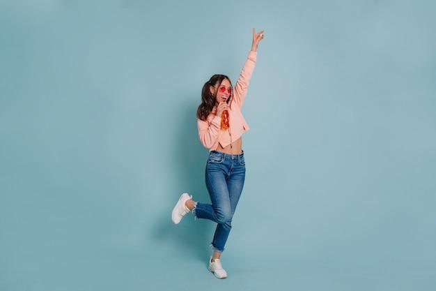 분홍색 스웨터와 분홍색 둥근 안경 춤과 격리 된 벽에 주스를 마시는 입고 젊은 매력적인 여자의 전체 길이 스튜디오 사진