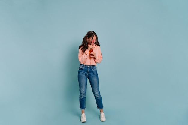 Ritratto a figura intera in studio di donna moderna ed elegante che indossa un maglione rosa e jeans in bicchieri rosa, bere succo e posa durante il servizio fotografico