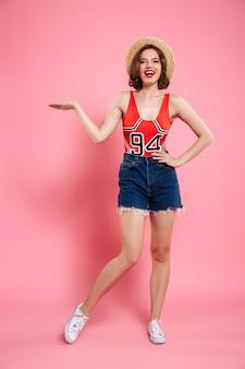 빨간 bodysuits와 청바지에 쾌활 한 irl의 전체 길이 초상화 빈 손바닥을 보여주는 그녀의 허리에 손으로 서