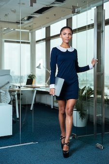 手にラップトップを持ってドアの近くに立って、オフィスでカメラを見ているドレスを着たフルレングスのアフロビジネス女性