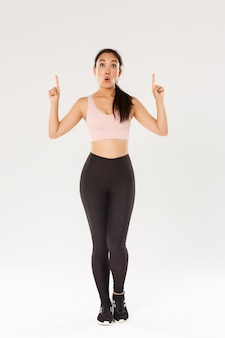 Full length of amazed and impressed asian female athelte, sportswoman in sportwear looking and pointing fingers up with excited face. fitness girl wondered with special offer in sports store.