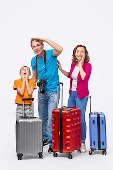 夏の旅行中にスーツケースの後ろに立っている間、完全な長さの驚いた両親と息子が距離を見て