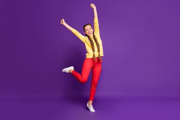 Полная длина удивительная дама с длинными косами, поднимающая руки, радуясь поддержке футбольной команды, носит повседневный желтый пуловер, красные брюки, изолированные на стене фиолетового цвета
