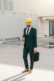 Full length of architect in formal wear and with yellow helmet on head holding briefcase and plans while standing at construction site.