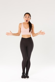 Full length of astonished and surprised female athlete, sportswoman in activewear looking impressed, drop jaw and spread hands sideways see great gym discount, workout equipment in sale.