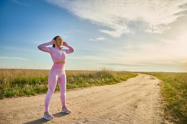 Женщина-спортсменка в полный рост в наушниках и стильной розовой спортивной одежде стоит на степной дороге, готовая совершить пробежку на природе в свете заката