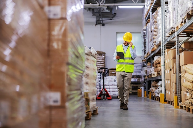 Full length of attractive bearded supervisor with protective helmet in west walking around warehouse and holding tablet to check on goods for shipment.