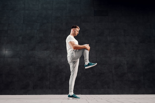 Full length of attractive caucasian bearded blonde man standing on one foot and stretching leg.
