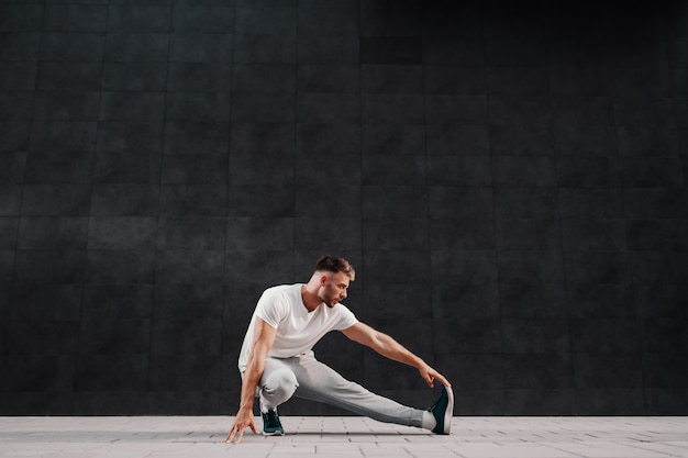 Full length of attractive caucasian bearded blonde man stretching leg.