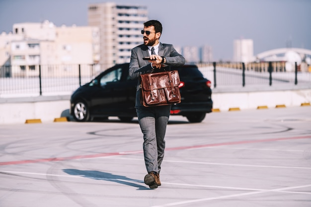 Full length of attractive caucasian bearded businessman in suit with sunglasses holding briefcase, walking on parking lot and rushing to get on time on meeting.
