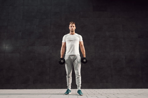 Full length of attractive caucasian muscular bearded blonde man in tracksuit and with t-shirt standing in front of gray wall and holding dumbbells.
